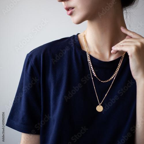 Fotografija Closeup photo of yping woman wearing dark t-shirt and golden necklace