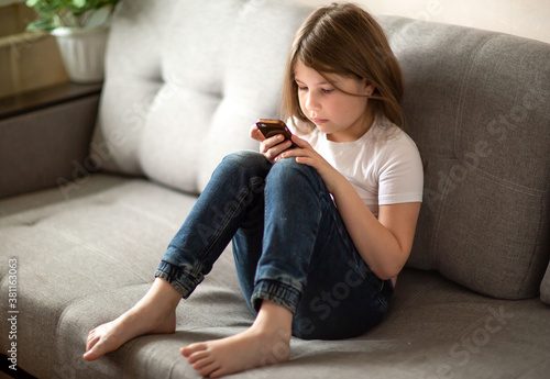 Vászonkép the child sits on the couch and talks on the phone