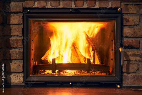 Fototapeta fireplace and fire close view as object or background, brick wall obraz