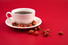 Rosehip Scattered On A Saucer And A Red Background. Autumn Background. The Concept Of Healthy Drinks.