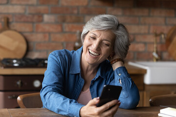 Fototapeta Boks Excited mature Caucasian grey-haired woman sit at table at home laugh watch funny video on smartphone online. Happy senior 60s female have fun using modern cellphone. Elderly and technology concept