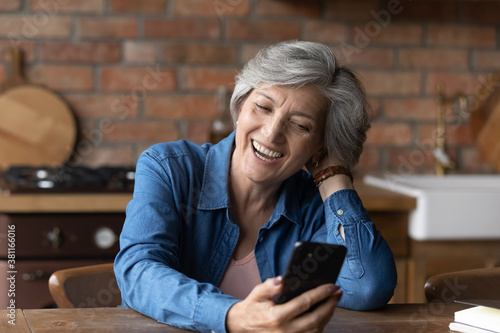 Excited mature Caucasian grey-haired woman sit at table at home laugh watch funny video on smartphone online. Happy senior 60s female have fun using modern cellphone. Elderly and technology concept