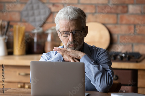 Fototapeta Pensive senior Caucasian grey-haired man look at laptop screen thinking of problem solution. Thoughtful mature grey-haired 70s male work on computer, pondering. Elderly and technology concept obraz