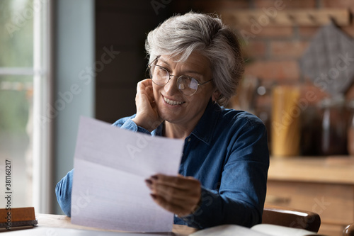 Fototapeta Happy mature 60s woman in glasses sit at table manage paperwork read postal letter correspondence