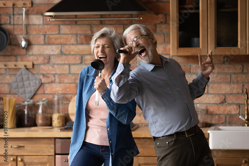 Happy senior husband and wife have fun sing in kitchen appliances cooking together at home Fototapet