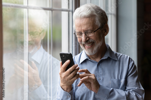 Foto Happy senior Caucasian man in glasses look at cellphone screen browse wireless internet