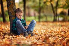 A Boy Sits In An Autumn Park U...