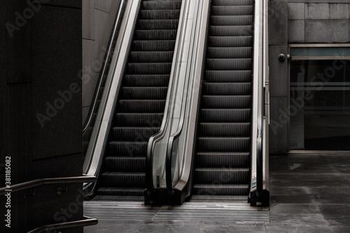 Fototapeta Grayscale shot of escalators in a building at daylight