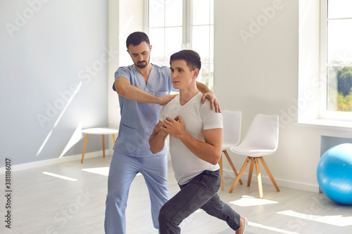 Physiotherapist in medical center helping young male athlete recover after sport Fotobehang