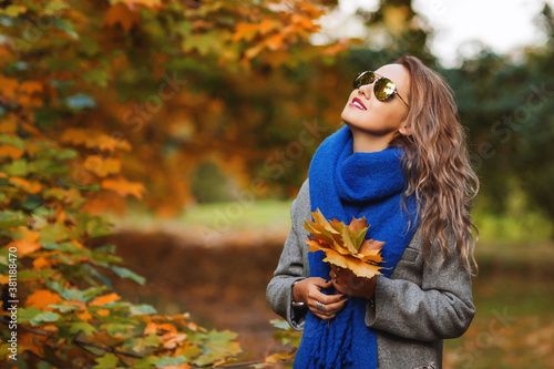 Fotomural Outdoors lifestyle fashion image of happy pretty girl walking on the sunny autumn park