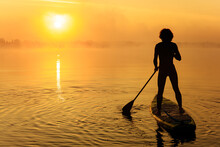 Young Man In Silhouette Standing On Sup Board During Sunrise