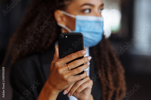 Young businesswoman wearing a medical mask stands near the office center Canvas Print