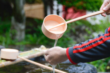 A Visitor Of The Shrine Taking The Holy Water Using A Water Ladle To Wash His Hand