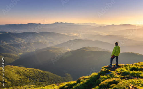 Fototapeta Sporty man on the mountain peak looking on mountain valley with sunbeams at colorful sunset in autumn in Europe. Landscape with traveler, foggy hills, forest in fall, amazing sky and sunlight in fall obraz