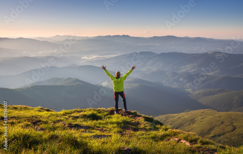 Obraz na plátně Sporty man standing on the mountain peak with raised up arms against mountain valley in fog at sunset in autumn