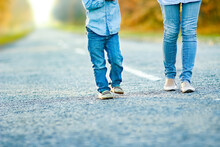 A Happy Parent With Child Are Walking Along The Road In The Park On Nature Travel