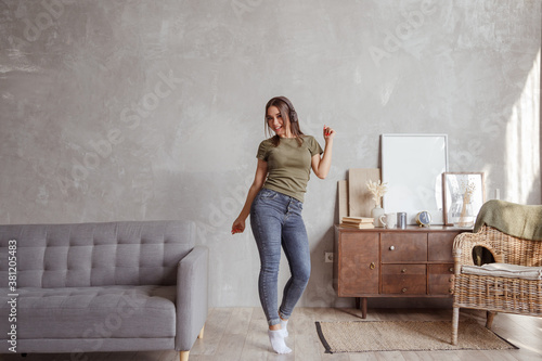 Obraz na plátně Young woman with wireless headphones dancing and listening to music at home