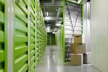 Background Image Of Green Self Storage Facility With Opened Unit Door And Cardboard Boxes, Copy Space