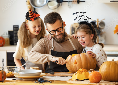 happy family   father and children prepare for Halloween by carving pumpkins at home in kitchen Fototapet