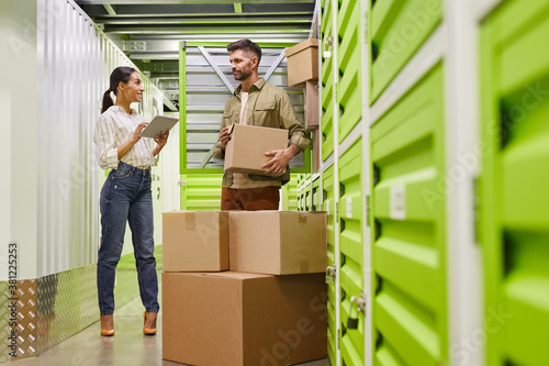 Fototapeta Full length portrait of modern couple using digital tablet while loading boxes into self storage container, copy space obraz