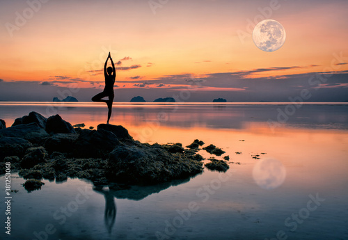 Fototapeta Silhouette of a young woman standing on the rocks by the sea in a yoga pose against the backdrop of a spectacular sunset and a huge rising full moon on a summer evening obraz