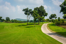 The Road Way For Golf Cart And Golfer  In Golf Course With Green Grass ,green Trees Blue Sky White Clouds Background