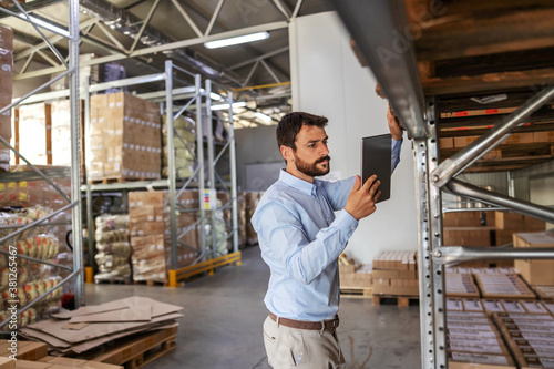 Fototapeta Young attractive bearded supervisor standing next to shelves in warehouse and checking on goods while holding and looking at tablet. obraz