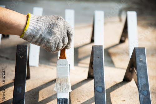 Photo Man is coating white color for steel furniture part - painter at work concept
