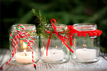 Cozy Handmade Holiday Home Decor. Christmas Decoration With Candles In Glass Jars Decorated Red Ribbon.