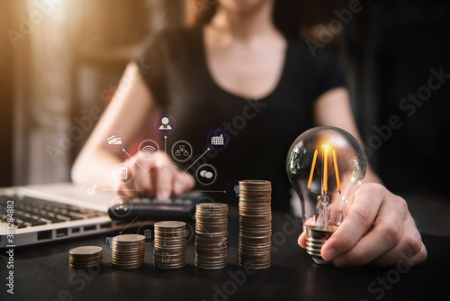 businessman hand holding lightbulb with using laptop computer and money stack in office Poster Mural XXL