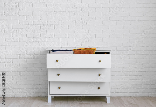 Fototapeta Modern chest of drawers with clothes near brick wall in room obraz