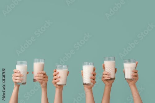 Female hands with glasses of vegan milk on color background