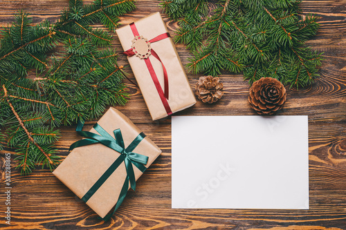 Fototapeta Beautiful Christmas gifts with empty card on wooden background obraz