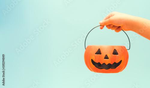 Fototapeta Toddler kid hands holding jack-o-lantern bucket ready for halloween. Children with candy bucket on blue background.Child having fun at Halloween trick or treat.Kids trick or treating.Autumn October obraz