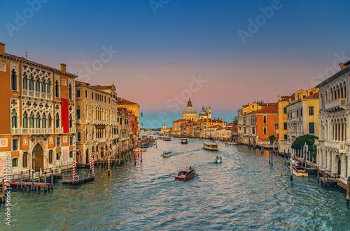 Fototapeta Venice cityscape with Grand Canal waterway. Buildings with evening lights along Grand Canal. Santa Maria della Salute Roman Catholic church on Punta della Dogana at twilight. Veneto Region, Italy. obraz