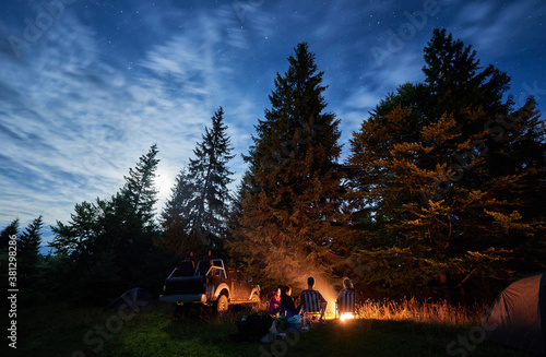 Fototapeta Group of friends near campfire, pickup offroad truck, tents at night camp in the mountains surrounded by spruce trees under magical starry sky, rear view. Car travel and camping concept obraz na płótnie