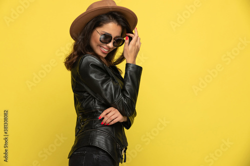 timid young girl in leather jacket arranging hair and smiling