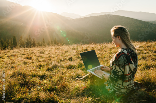 Fototapeta Hipster woman working with laptop sitting in mountains. Hiker tourist enjoying valley view sunset. Vacation holidays in autumn day. Distant remote work and travel, freelance as lifestyle concept. obraz