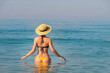 An attractive slender young Caucasian woman in a swimsuit and a straw hat stands waist-deep in sea water in the morning when there is haze over the sea