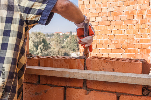 Fotografiet Bricklayer worker installing brick masonry on exterior wall with trowel