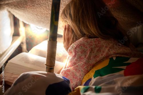 Photo fille en train de lire dans sa cabane
