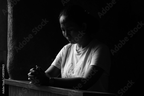 Valokuvatapetti Portrait of young woman kneeling and praying in silent prayer pose, on black and white background