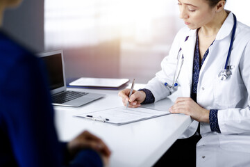 Unknown woman-doctor is writing some medical recommendations to her patient, while they are sitting together at the desk in the sunny cabinet in a clinic. Physician is using a clipboard, close-up