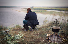 Man Sitting On The River Beach