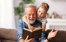. Cheerful Grandfather And Grandson Reading Book Together.
