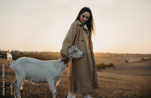 Fotografie, Tablou Shepherdess stands in a pasture near goat and embraces it.