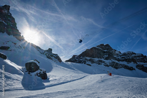 Fotografie, Obraz View of a ski resort piste with people skiing in Dolomites in Italy with cable car ski lift