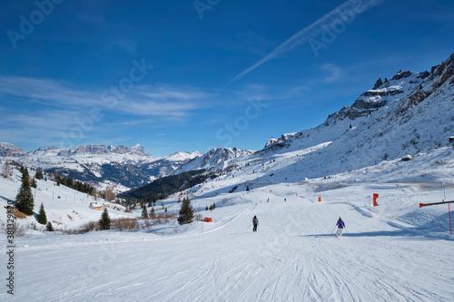 View of a ski resort piste with people skiing in Dolomites in Italy. Canazei, Italy