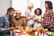 excited multicultural family talking while celebrating thanksgiving at table with festive dinner