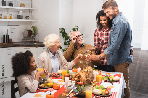 excited multiethnic family clinking wine glasses while celebrating thanksgiving day